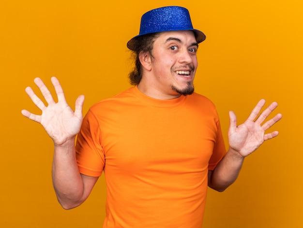 Aufgeregt aussehende kamera junger mann mit partyhut, der die hände isoliert auf der orangefarbenen wand ausbreitet