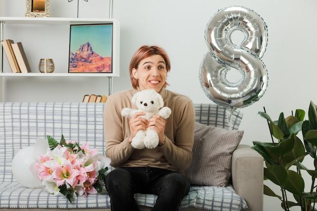 Aufgeregt aussehender seitlich gutaussehender kerl am glücklichen frauentag mit teddybär, der auf dem sofa im wohnzimmer sitzt