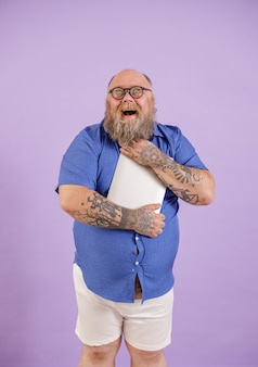 Aufgeregt bärtiger fettleibiger mann in engem blauem hemd mit brille umarmt modernen laptop auf violettem hintergrund im studio
