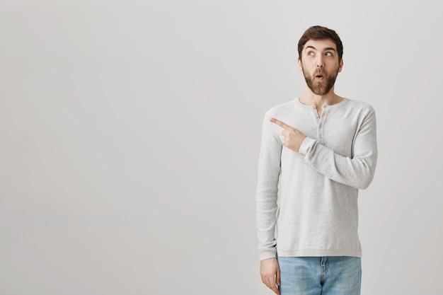 Aufgeregt beeindruckt mann zeigt finger links auf werbung