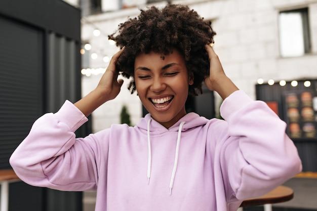 Aufgeregt charmante emotionale brünette frau in übergroßem lila hoodie lächelt und kräuselt die haare im freien
