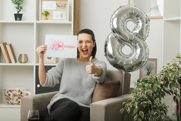Aufgeregt, daumen hoch, schönes mädchen am glücklichen frauentag, der eine grußkarte auf einem sessel im wohnzimmer hält