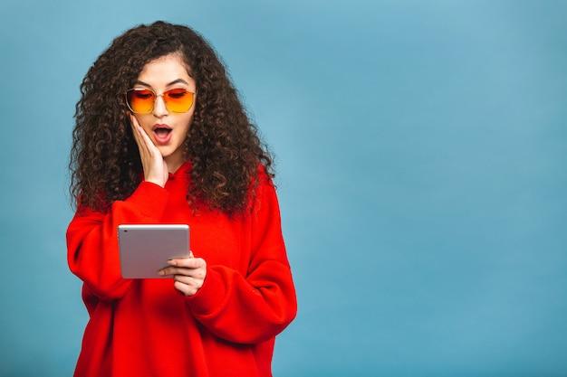 Aufgeregt erstaunt junge schöne frau mit tablet-pc. glückliches mädchen, das tablet-computer verwendet, lokalisiert auf blauem hintergrund.