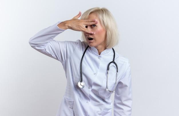 Aufgeregt erwachsene slawische ärztin in medizinischer robe mit stethoskop, die durch ihre finger in die kamera schaut, isoliert auf weißem hintergrund mit kopierraum