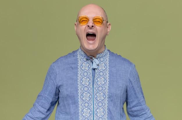 Aufgeregt erwachsener slawischer mann im blauen hemd mit sonnenbrille schreien