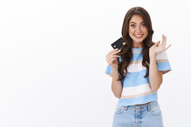 Aufgeregt fröhliche moderne frau hält kreditkarte und gestikuliert erfreut, breit lächelnd, freund gab dem bankkonto viel geld ein passwort, um bargeld zu verschwenden, online-shops zu bezahlen, einzukaufen