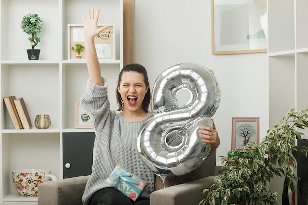 Aufgeregt, fünf schöne mädchen an einem glücklichen frauentag zu zeigen, der den ballon nummer acht hält, der auf einem sessel im wohnzimmer sitzt