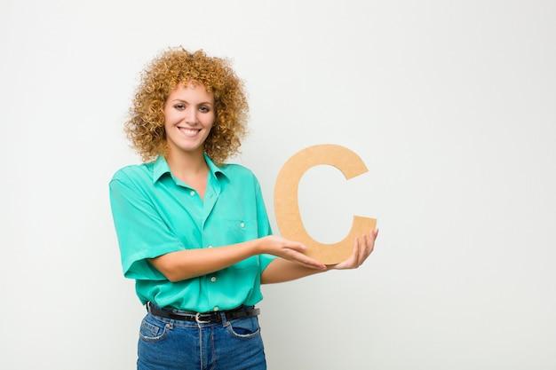 Aufgeregt, glücklich, freudig, den buchstaben c des alphabets haltend, um ein wort oder einen satz zu bilden.