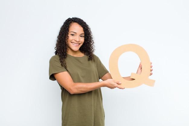 Aufgeregt, glücklich, freudig, den buchstaben q des alphabets haltend, um ein wort oder einen satz zu bilden.