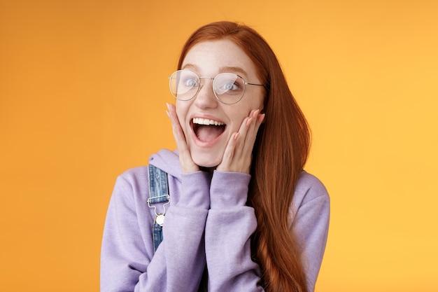 Aufgeregt glücklich lächelnd breit rothaarige freundin fallen kiefer grinsend aufgeregt blick links erstaunte berührung wangen reagieren ehrfürchtige atemberaubende nachrichten schreien glück, stehend orangefarbenen hintergrund.