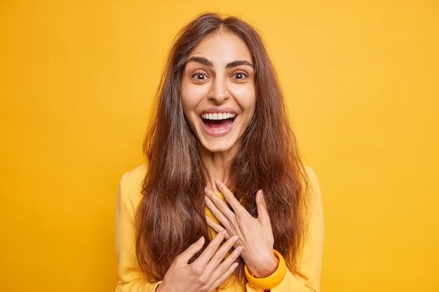 Aufgeregt glückliche europäische frau mit natürlichen langen haaren lächelt im großen und ganzen hört ausgezeichnete nachrichten