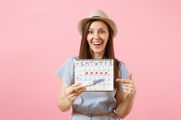 Aufgeregt glückliche frau in blauem kleid, hut in der hand halten schwangerschaftstest, periodenkalender zur überprüfung der menstruationstage einzeln auf rosafarbenem hintergrund. medizin, gesundheitswesen, gynäkologisches konzept. platz kopieren.