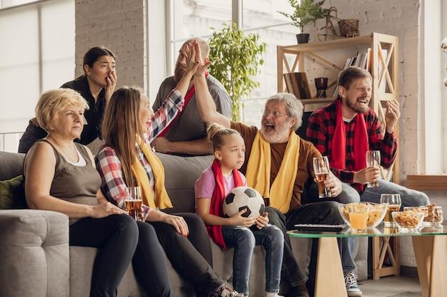 Aufgeregt, glückliche große familie, die fußball guckt, fußballspiel auf der couch zu hause. fans emotionaler jubel für lieblingsnationalmannschaft. spaß von den großeltern bis zu den kindern. sport, fernsehen, meisterschaft.