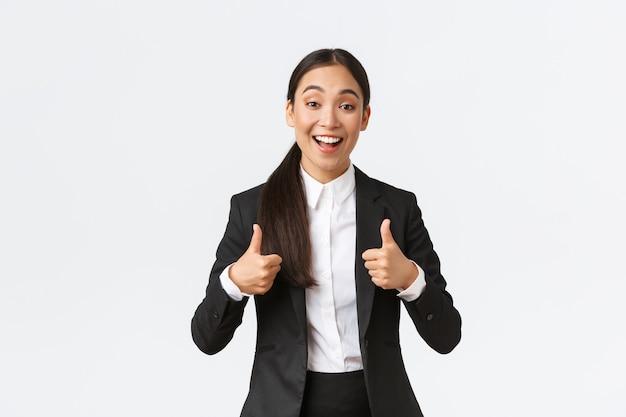 Aufgeregt glückliche verkäuferin lobt die arbeit von freunden, zeigt daumen hoch zur zustimmung und lächelt überrascht, gratuliert mit viel. geschäftsfrau mit erstaunlichem ergebnis zufrieden