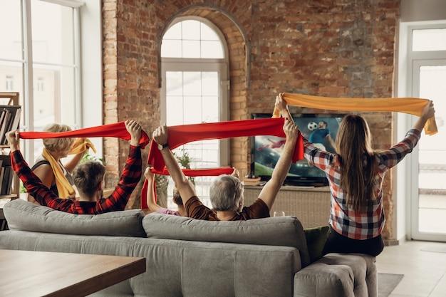 Aufgeregt, glückliches großes familienteam, das zusammen sportmatch auf der couch zu hause ansieht