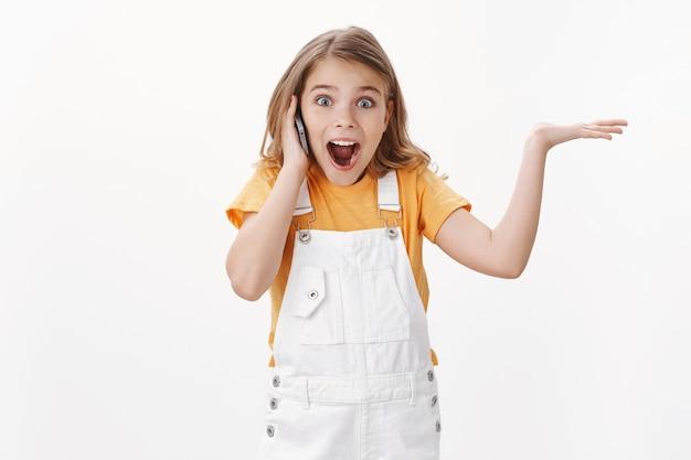 Aufgeregt glückliches süßes kleines mädchen, das angenehme tolle nachrichten über das smartphone hört, die hand aufregt und überglücklich macht, das handy in der nähe des ohrs halten, den mund begeistert öffnen, emotional reagieren, weiße wand