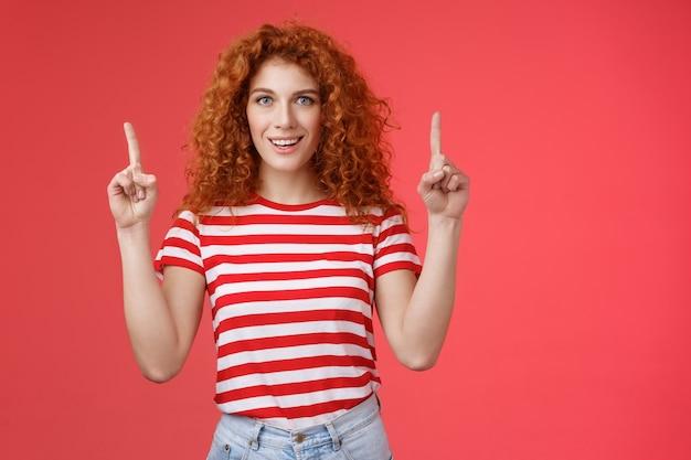 Aufgeregt gut aussehende freche rothaarige ingwer mädchen lockiges natürliches haar zeigt erhobenen zeigefinger nach oben lächelnd beeindruckt begeistert beratung store regie promo werbung tolles haarpflegeprodukt.
