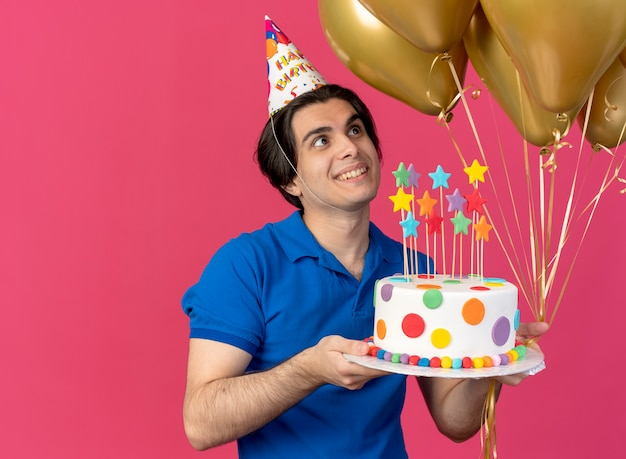 Aufgeregt gut aussehender kaukasischer mann mit geburtstagsmütze hält heliumballons und geburtstagskuchen