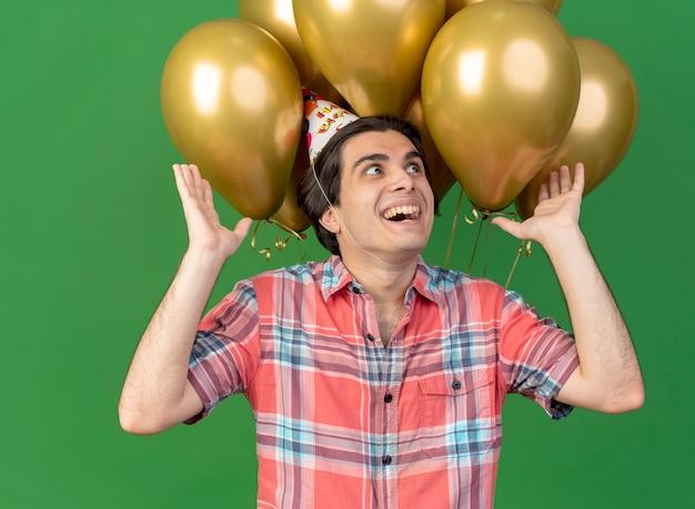 Aufgeregt gut aussehender kaukasischer mann mit geburtstagsmütze steht mit erhobenen händen vor heliumballons