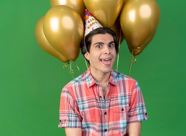 Aufgeregt gutaussehender kaukasischer mann mit geburtstagsmütze streckt die zunge vor heliumballons aus