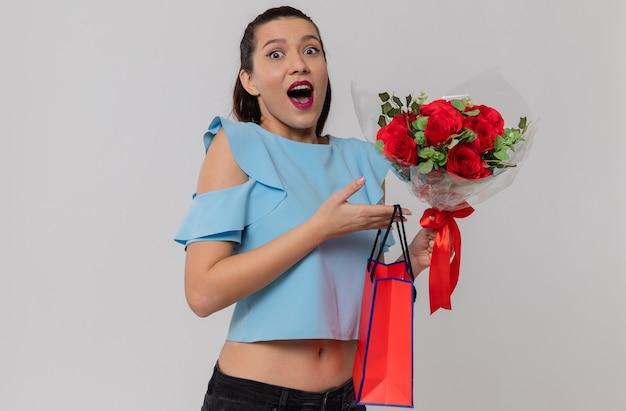 Aufgeregt hübsche junge frau mit blumenstrauß und geschenktüte