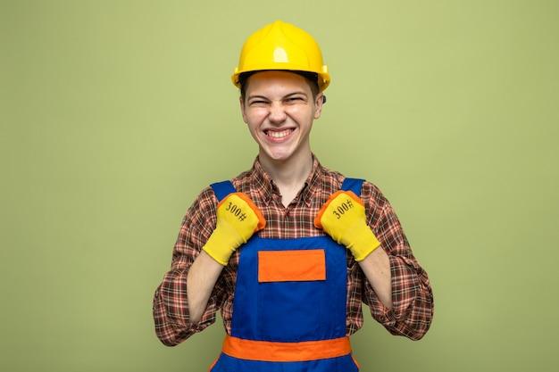 Aufgeregt, ja geste junger männlicher baumeister zu zeigen, der uniform mit handschuhen trägt
