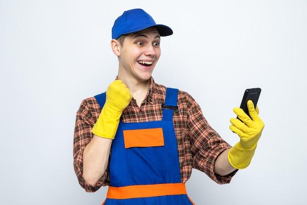 Aufgeregt, ja, geste junger putzmann in uniform und mütze mit handschuhen, die das telefon halten und betrachten
