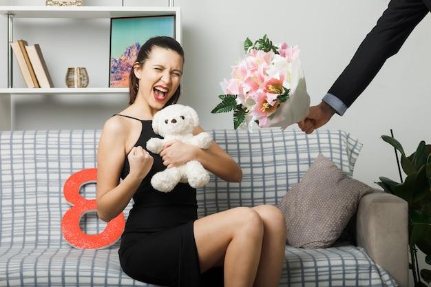 Aufgeregt, ja geste junges mädchen am glücklichen frauentag zu zeigen, der auf dem sofa sitzt und teddybär im wohnzimmer hält