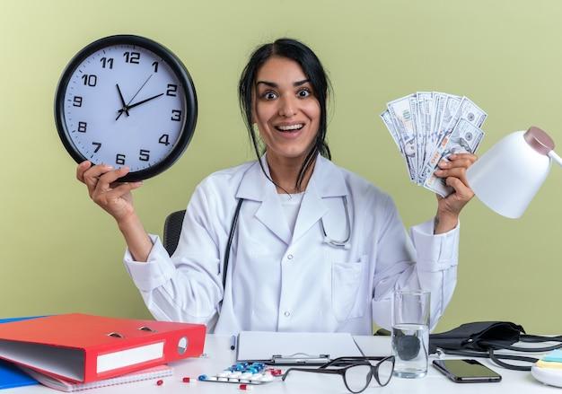 Aufgeregt junge ärztin, die medizinische robe mit stethoskop trägt, sitzt am schreibtisch mit medizinischen werkzeugen, die eine wanduhr mit bargeld isoliert auf olivgrüner wand halten