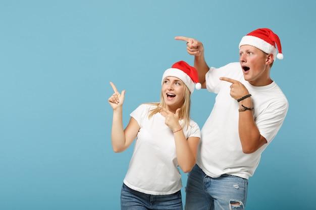 Aufgeregt junge santa paar freunde kerl und frau in weihnachtsmütze posiert