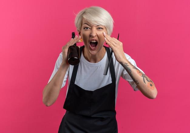 Aufgeregt junge schöne friseurin in uniform mit friseurwerkzeugen, die jemanden einzeln auf rosa wand anrufen
