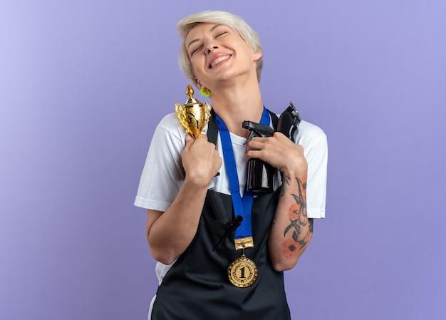Aufgeregt mit geschlossenen augen, die den kopf kippen, junge, schöne friseurin in uniform, die medaillen trägt, die friseurwerkzeuge und siegerpokal einzeln auf blauer wand halten
