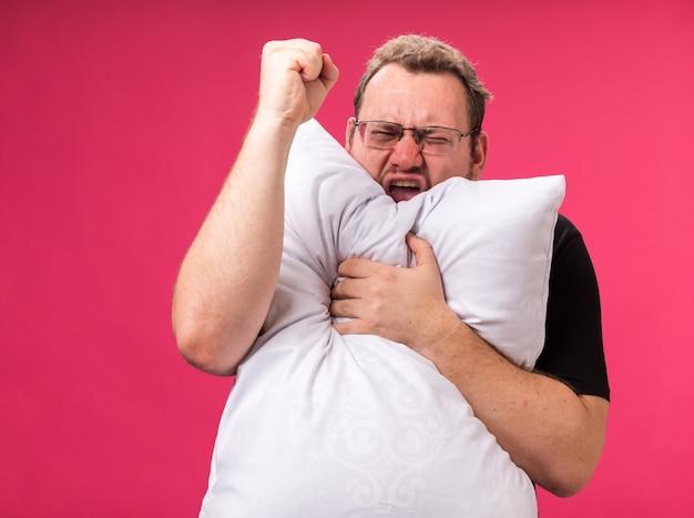 Aufgeregt mit geschlossenen augen, ein kranker mann mittleren alters umarmte das kissen, das eine ja-geste zeigt