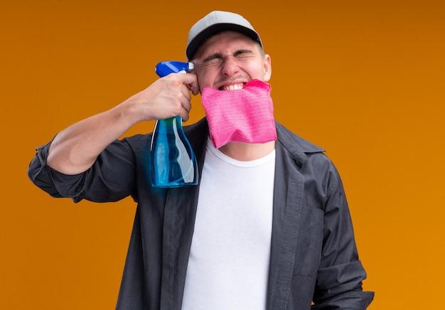 Aufgeregt mit geschlossenen augen junger hübscher putzmann, der t-shirt und kappe hält lappen im mund setzt sprühflasche auf schläfe isoliert auf orange wand