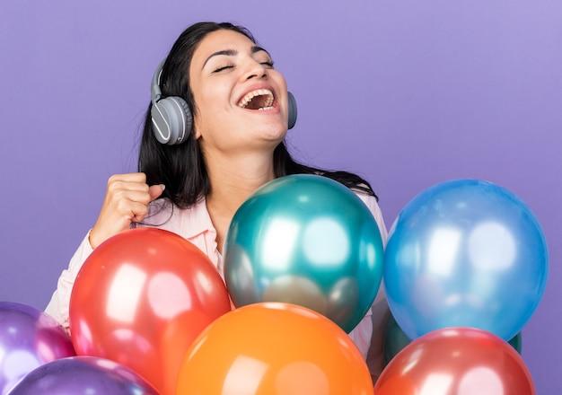 Aufgeregt mit geschlossenen augen junges schönes mädchen mit kopfhörern, die hinter luftballons stehen