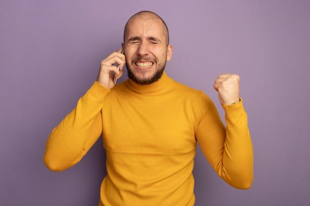 Aufgeregt mit geschlossenen augen spricht junger gutaussehender mann am telefon und zeigt ja geste isoliert auf lila wand