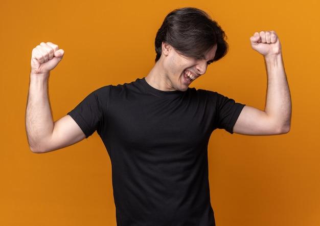 Aufgeregt mit gesenktem kopf, einem jungen, gutaussehenden kerl, der ein schwarzes t-shirt trägt und eine ja-geste einzeln auf der orangefarbenen wand zeigt