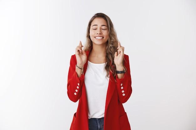Aufgeregt nervöse weibliche auszubildende hoffnung bekommen job kreuzfinger viel glück machen wunsch schließen augen lächeln verträumt hoffentlich beten traum wird wahr, steht aufgeregt und erwartet wunder weiße wand