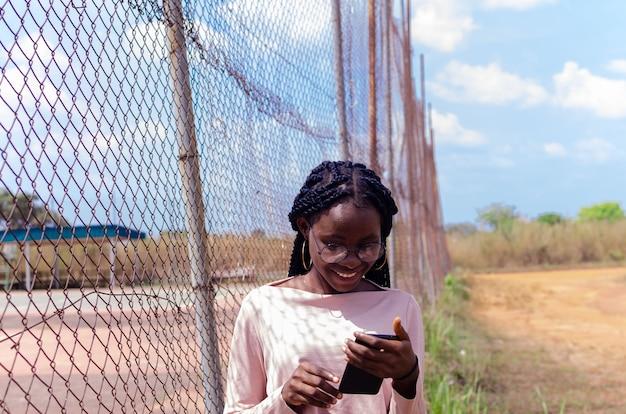 Aufgeregt schöne afrikanische dame, die ihr handy bedient