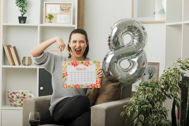 Aufgeregt schöne frau am glücklichen frauentag hält und zeigt auf den kalender, der auf einem sessel im wohnzimmer sitzt