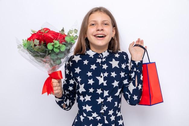 Aufgeregt schönes kleines mädchen am glücklichen valentinstag mit blumenstrauß mit geschenktüte