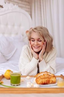 Aufgeregt sein. ansprechende frau, die sich vor dem frühstück im bett aufgeregt fühlt, während sie sich croissants ansieht
