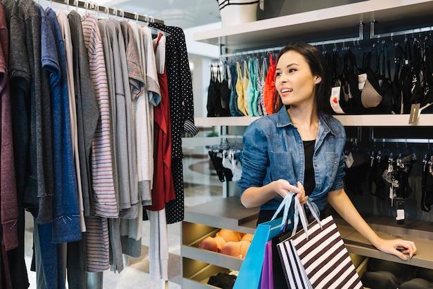 Aufgeregt shopper zu fuß unter kleidung auf kleiderbügel