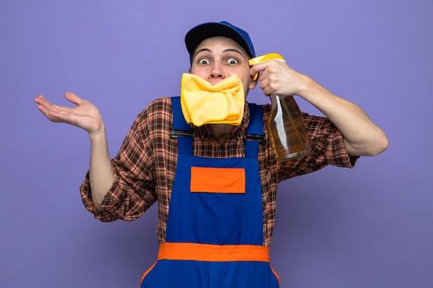 Aufgeregt sich ausbreitende hand junger putzmann mit uniform und mütze, der lappen in den mund steckt und reinigungsmittel auf dem kopf hält