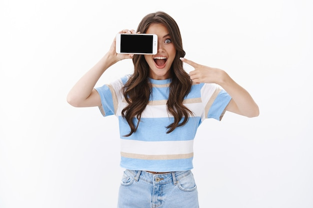 Aufgeregt sorglos lächelnde frau hält smartphone horizontale abdeckung ein auge mit handy, zeigt handy-display und offenen mund fasziniert, schauen sie sich die coole spiel-foto-app an, weiße wand