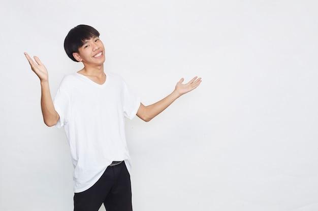 Aufgeregt überraschten niedlichen jungen asiatischen mann im lässigen weißen t-shirt, das offene handgeste auf grauer oberfläche tut