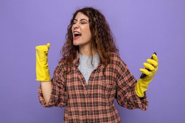 Aufgeregt zeigt ja geste junge putzfrau mit handschuhen, die das telefon isoliert auf lila wand hält
