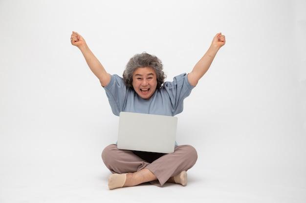 Aufgeregte ältere asiatische frau, die gewinner fühlt, der sieg online-geschäftserfolg feiert und auf dem boden mit laptop sitzt, freiberufliches reifes konzept