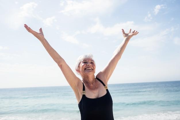Aufgeregte ältere frau, die am strand steht