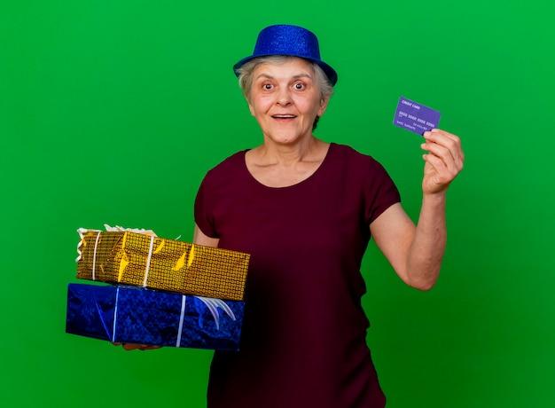 Aufgeregte ältere frau, die partyhut trägt, hält geschenkboxen und kreditkarte auf grün